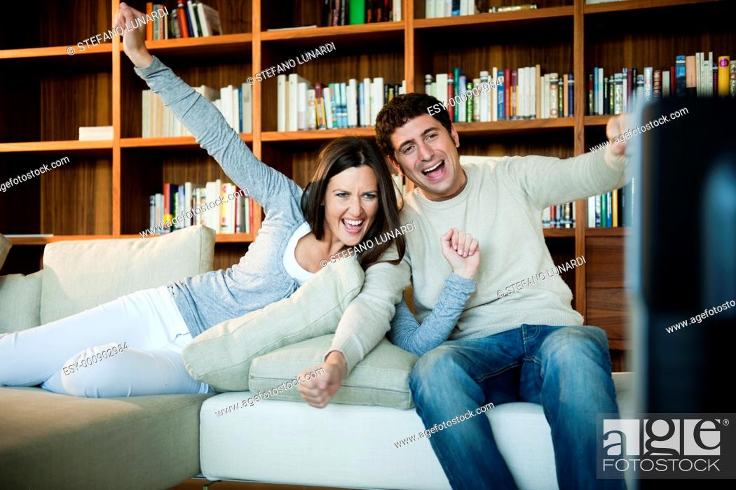 Stock Photo: Young couple celebrating while watching TV.