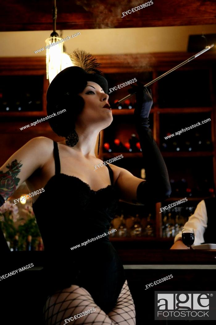Stock Photo: Young sexy woman smoking in burlesque bar.