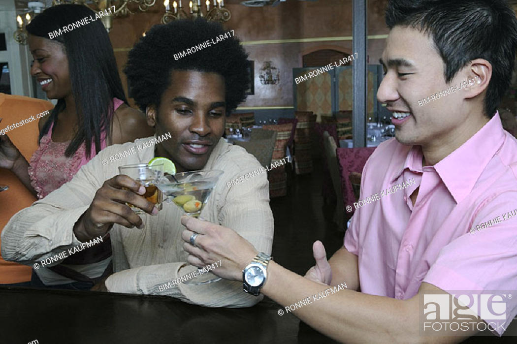 Stock Photo: Young men toasting each other.
