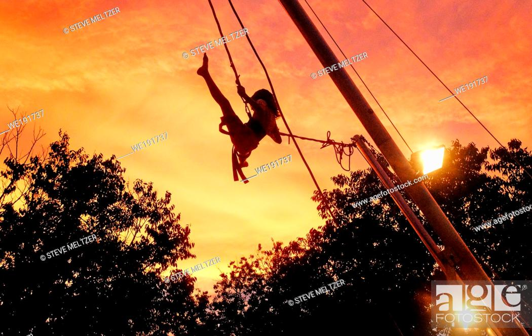 Stock Photo: A young girl pumps her legs high in the air to push her rope swing high into the air of an evening sunset, South of France near Pezenas,.