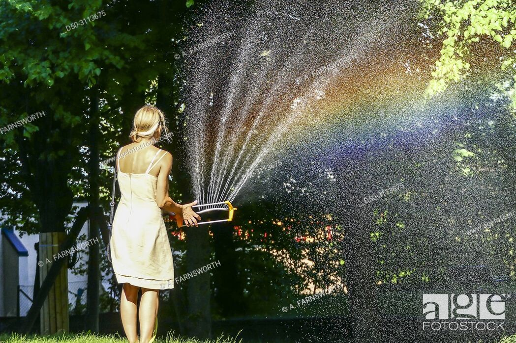 Stock Photo: A woman waters the grass with a hose in the Hagalund Park and apartment complex, Solna suburb. Stockholm, Sweden.