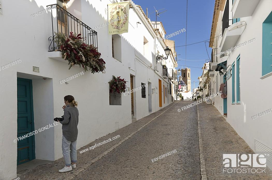 Photo de stock: Teen with his camera of photos walking through the streets of Altea, in the province of Alicante, Spain.