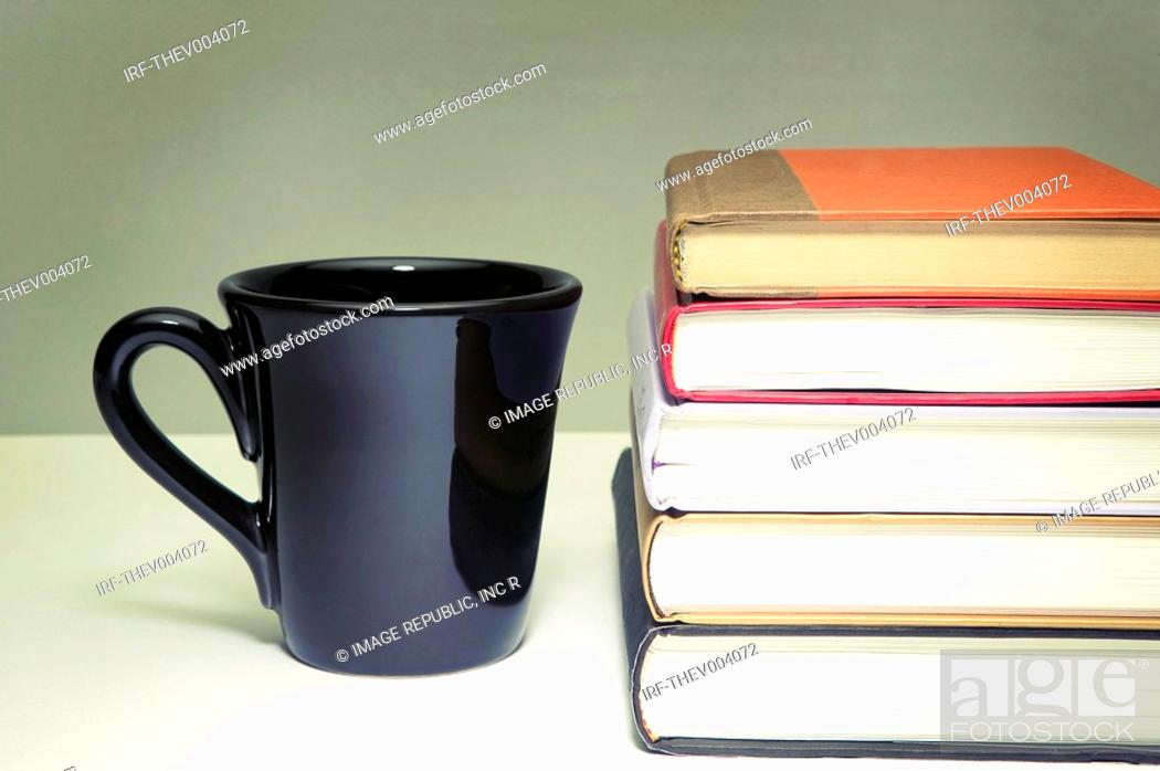 Stock Photo: pile of books and cup.