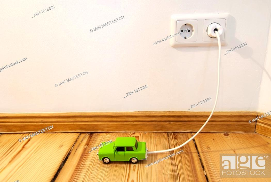 Stock Photo: Concept of toy electric car being recharged by plug-in connection to electric supply in the home.