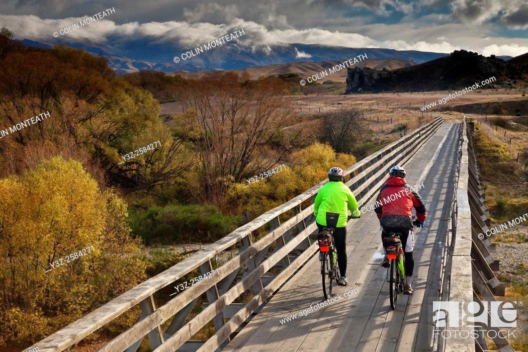 Stock Photo: Cyclists crossing bridge, Otago Rail Trail, Otago, New Zealand.