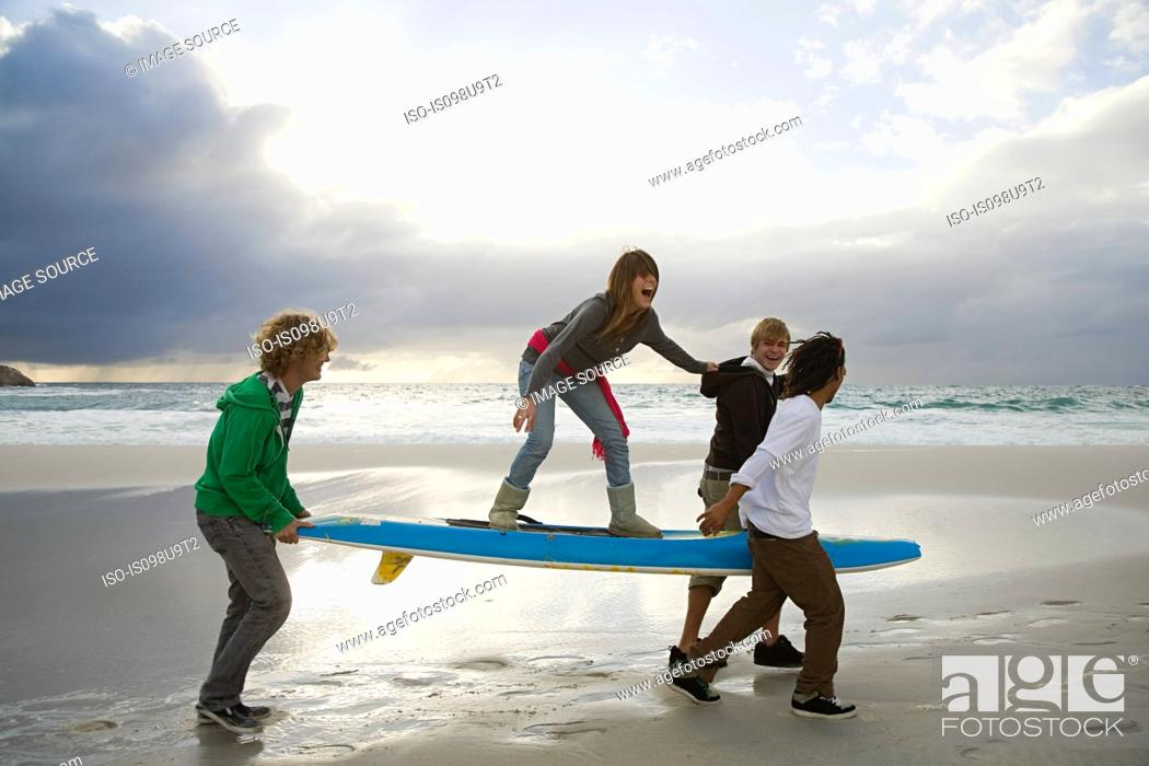 Stock Photo: Young people carrying surfboard, person balancing on top.