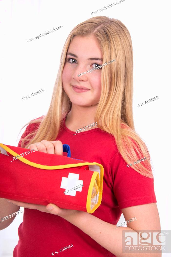 Stock Photo: young school girl, 15 year old, in red, with a broad smile, holding a first aid medical bag.