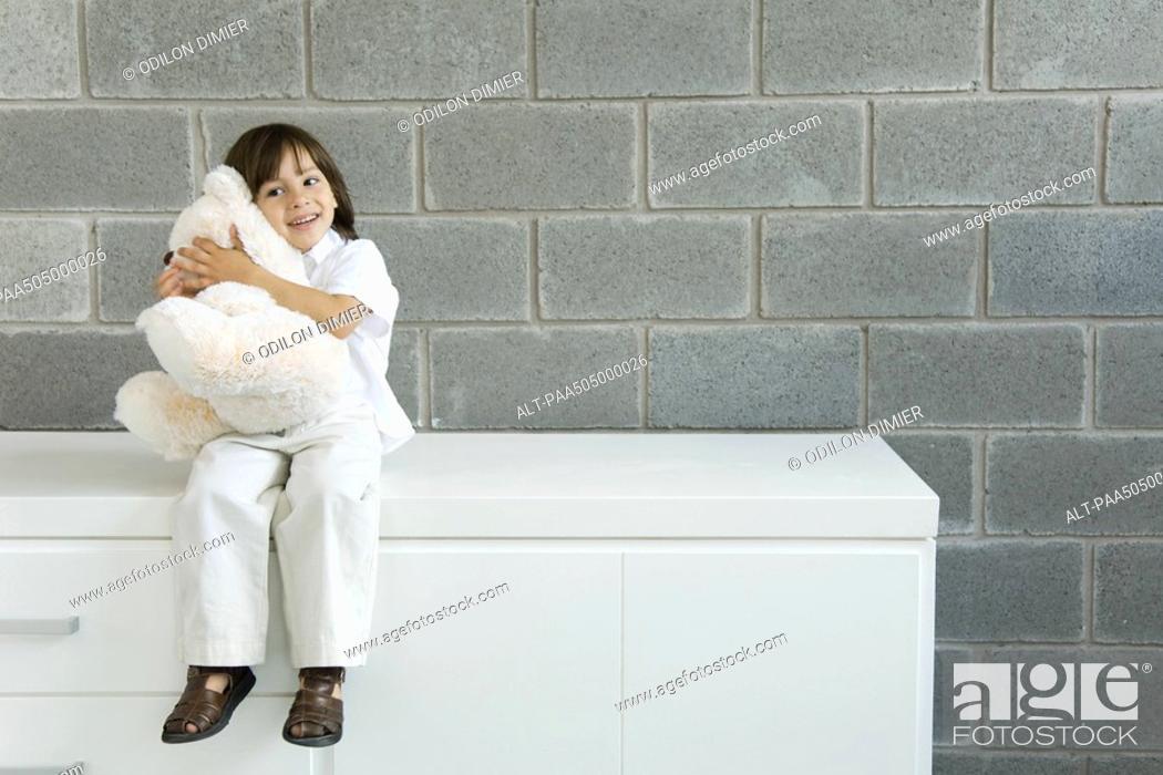 Stock Photo: Little boy sitting on counter, hugging teddy bear.