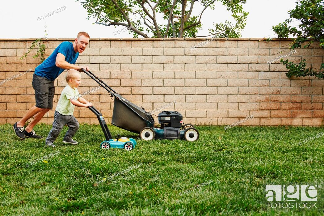 Stock Photo: Father and son mowing lawn in backyard.