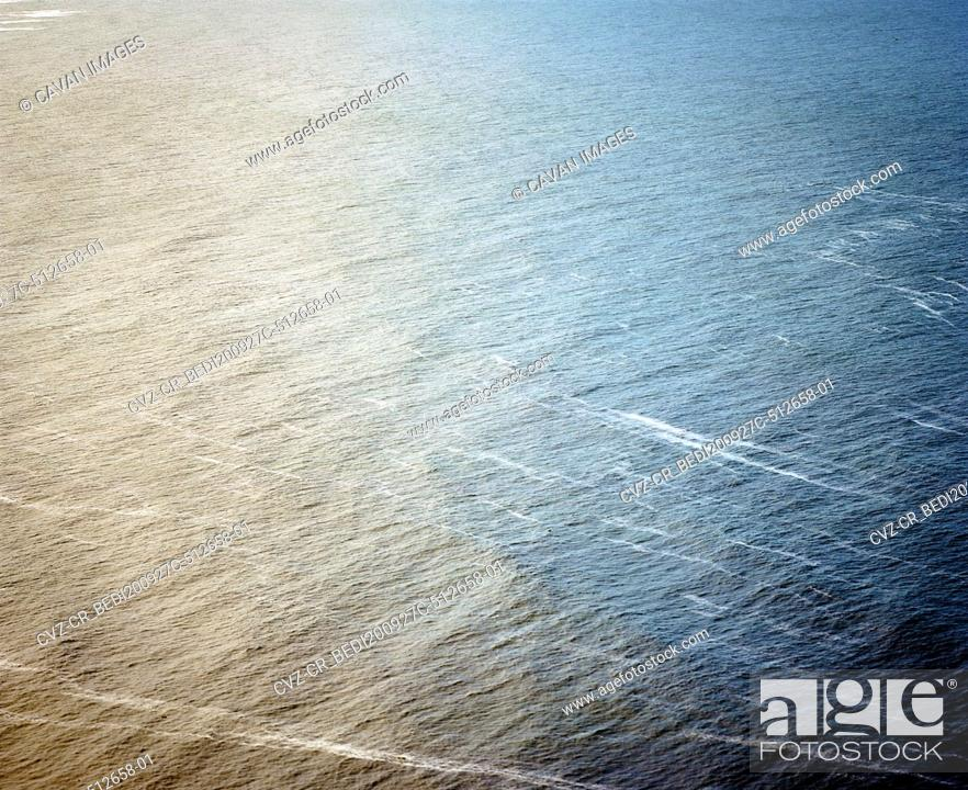 Stock Photo: Orange and blue water texture on the Pacific Ocean.