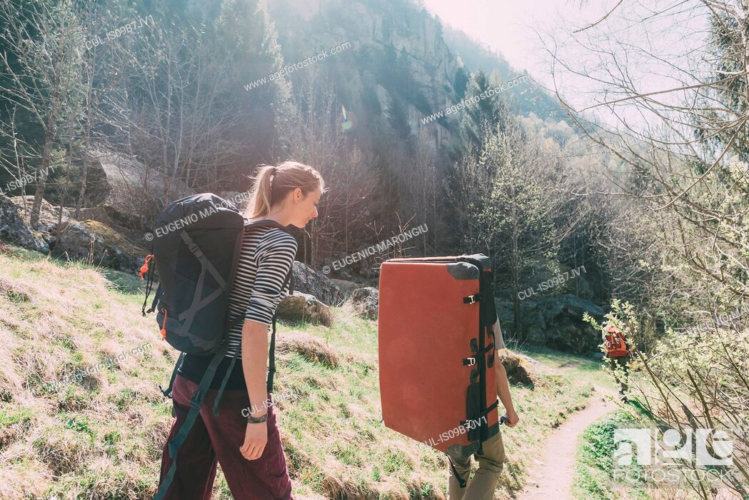 Stock Photo: Adult friends with bouldering mat backpack walking along rural path, Lombardy, Italy.