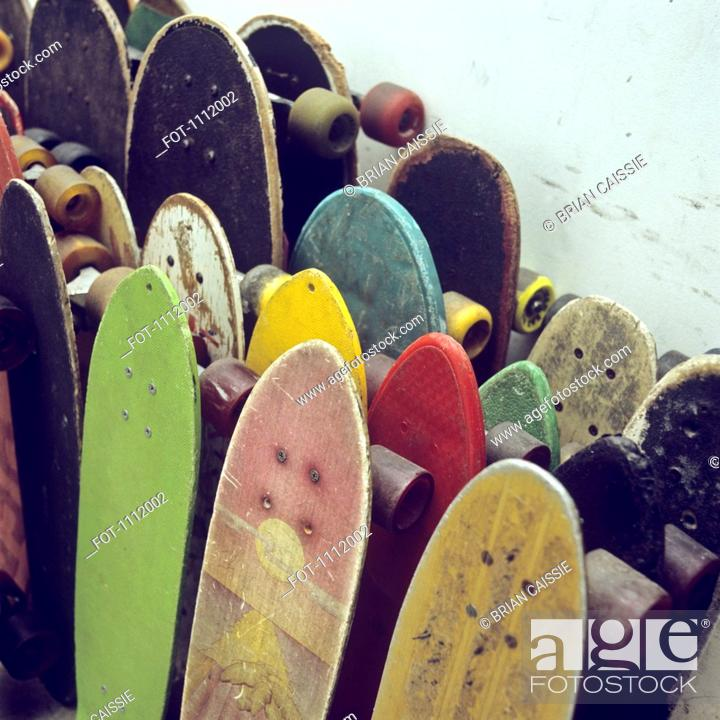 Stock Photo: Rows of used skateboards leaning against a wall.