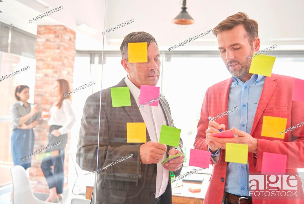 Stock Photo: View through glass of colleagues brainstorming using sticky notes.