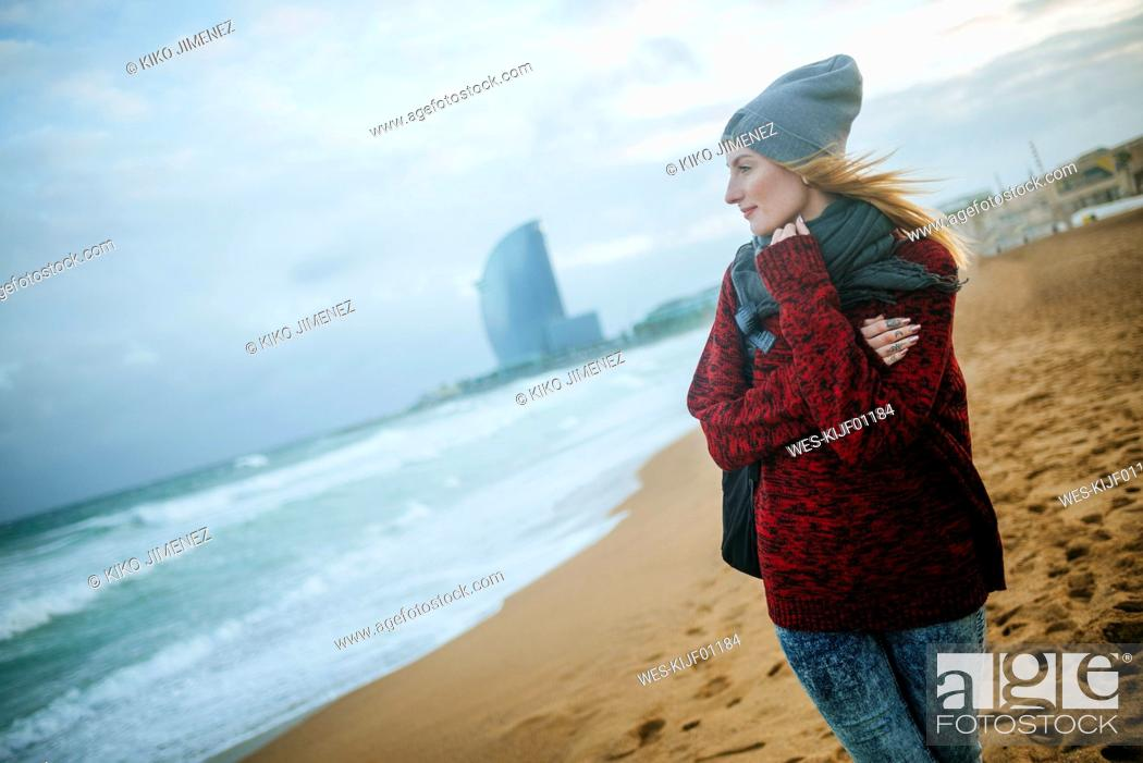 Photo de stock: Spain, Barcelona, young woman on the beach in winter.