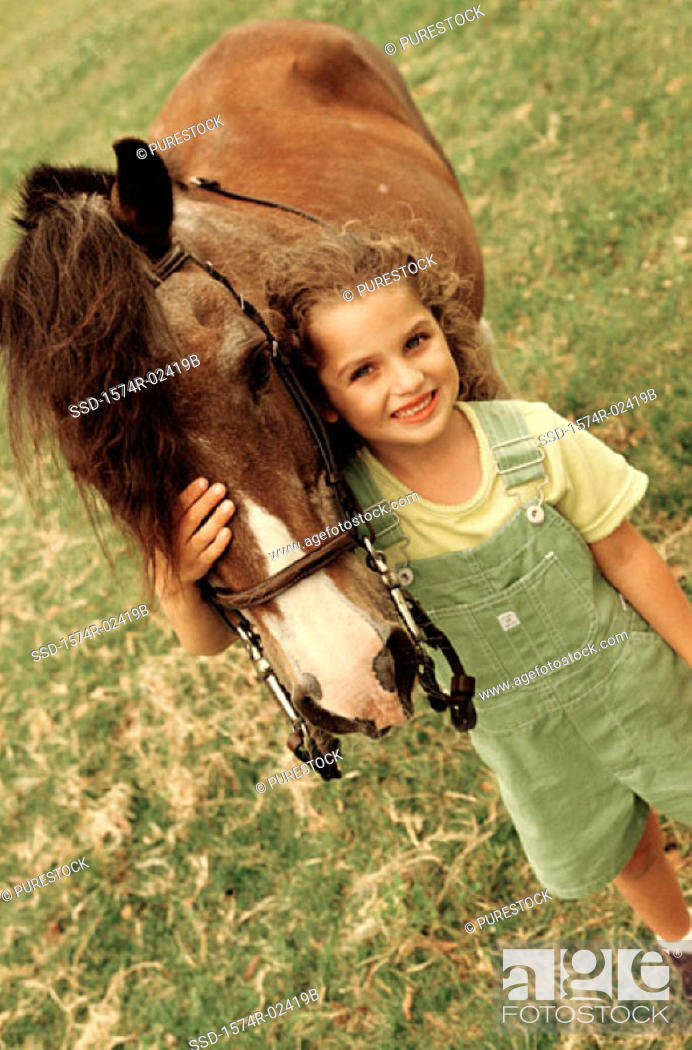 Stock Photo: High angle view of a girl standing with a horse.