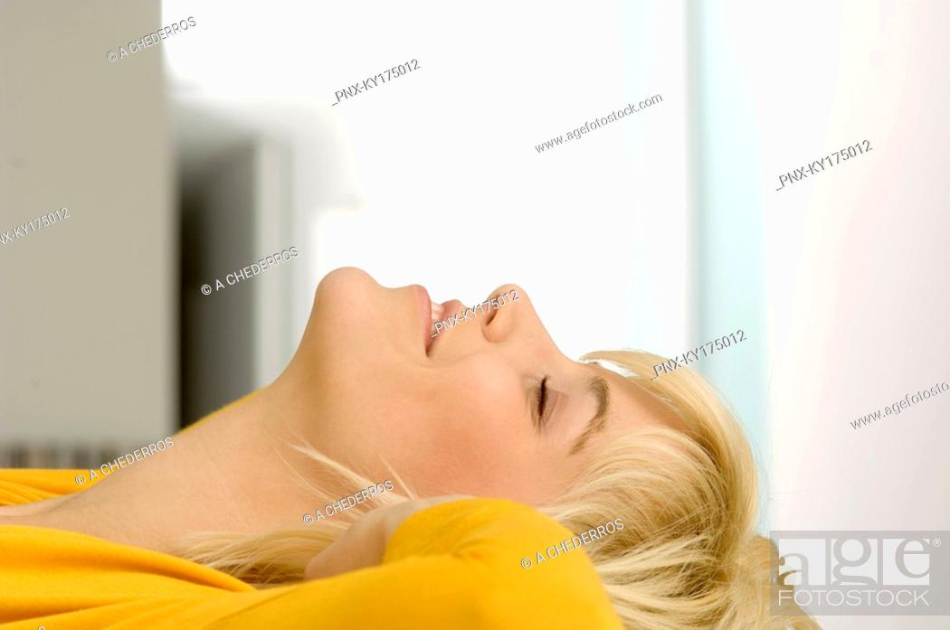 Stock Photo: Side profile of a young woman smiling with her eyes closed.