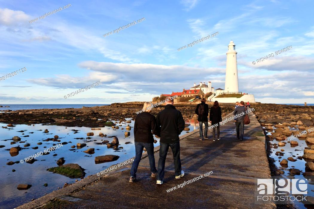Stock Photo: England, Northumberland, Whitley Bay. People walking across the concrete causeway to St Mary's Lighthouse near Whitley Bay.