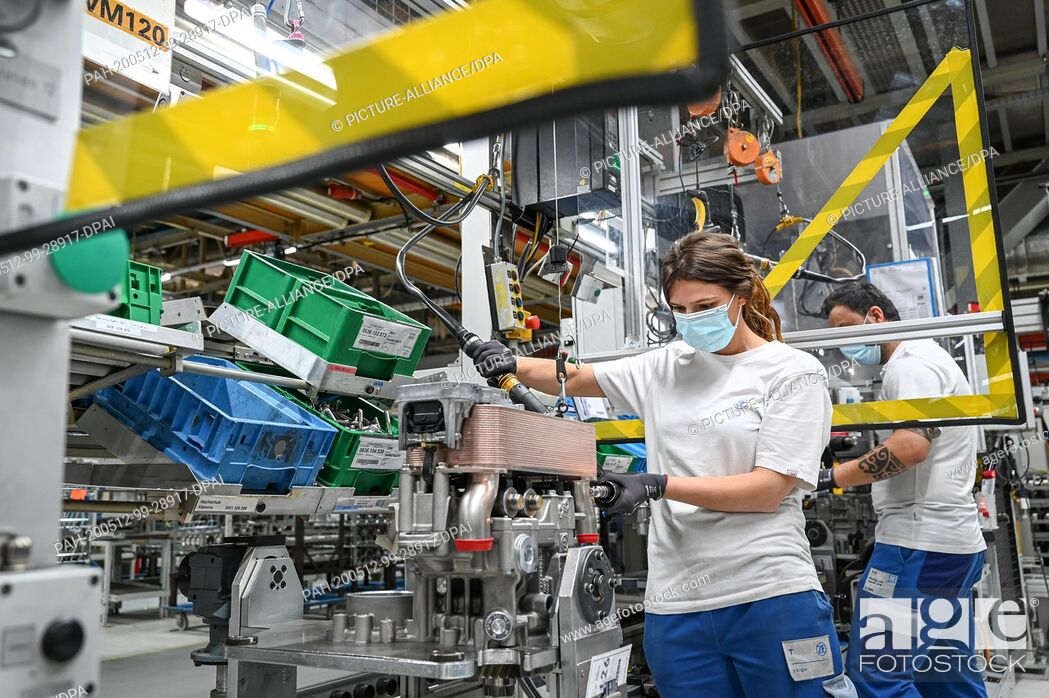Stock Photo: 12 May 2020, Baden-Wuerttemberg, Friedrichshafen: In plant two of the automotive supplier ZF Friedrichshafen, mechanic Vanessa is working on a transmission.