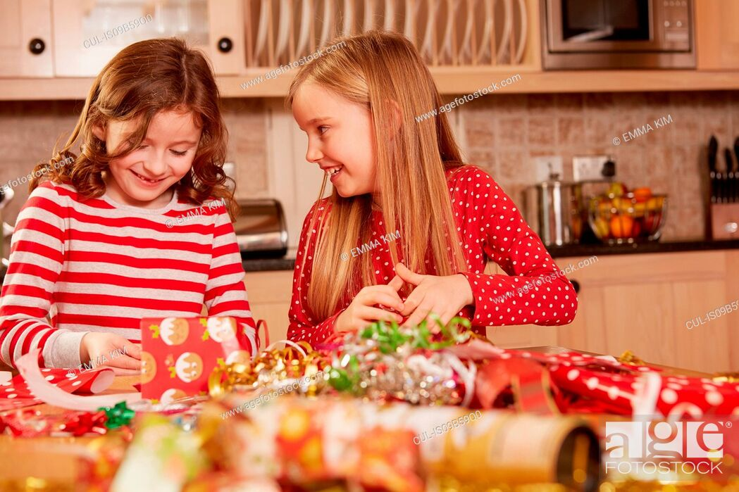 Imagen: Two girls wrapping christmas presents at table.
