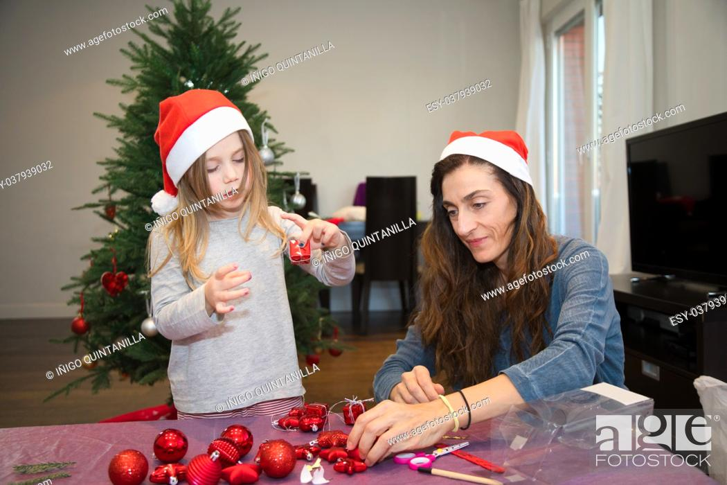 Stock Photo: four years blonde cute girl with red Santa Claus hat and her woman mother preparing adornments for the Christmas tree, at home.