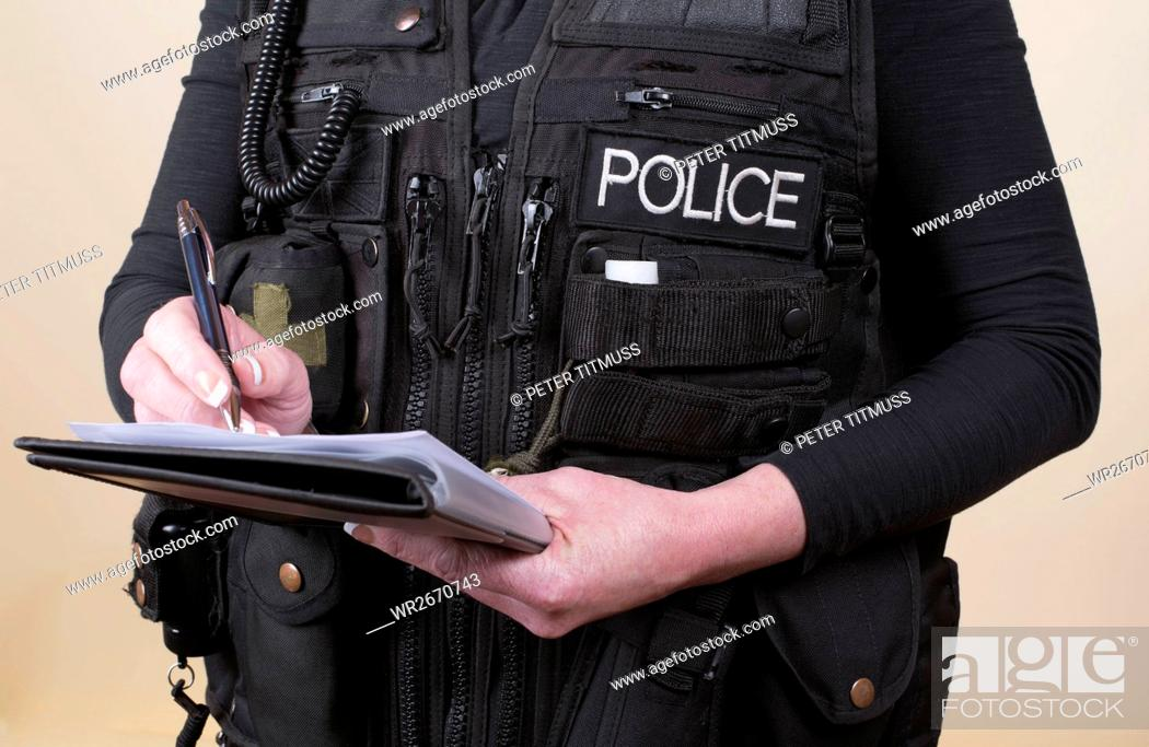Stock Photo: Police officer wearing tactical vest writing notes on a pad.