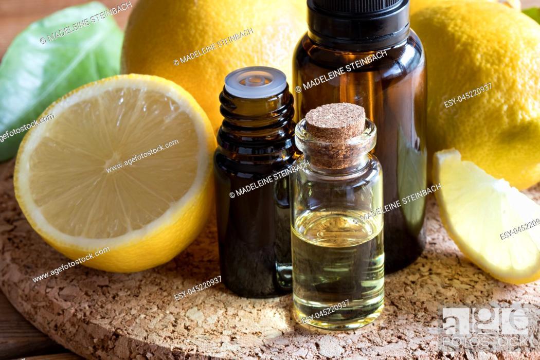 Stock Photo: Bottles of lemon essential oil with fresh lemons in the background.