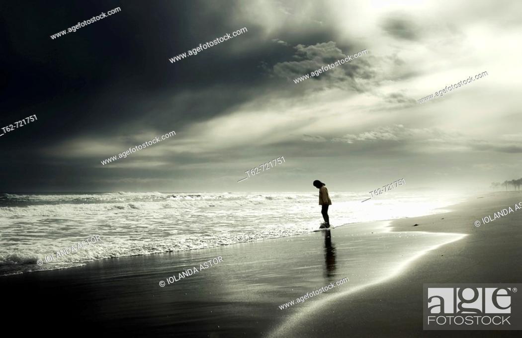 Stock Photo: Joven paseando solo por la orilla del mar en invierno.