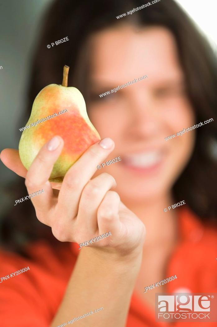 Stock Photo: Close-up of a pear in a woman's hand.