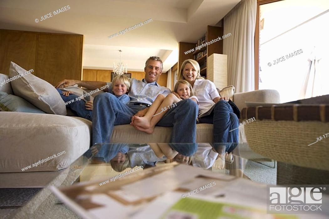 Stock Photo: Two generation family relaxing on sofa at home, smiling, front view, portrait.