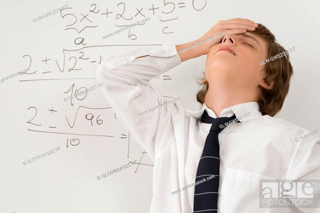 Stock Photo: Close-up of a teenage boy standing in front of a whiteboard and looking stressed.