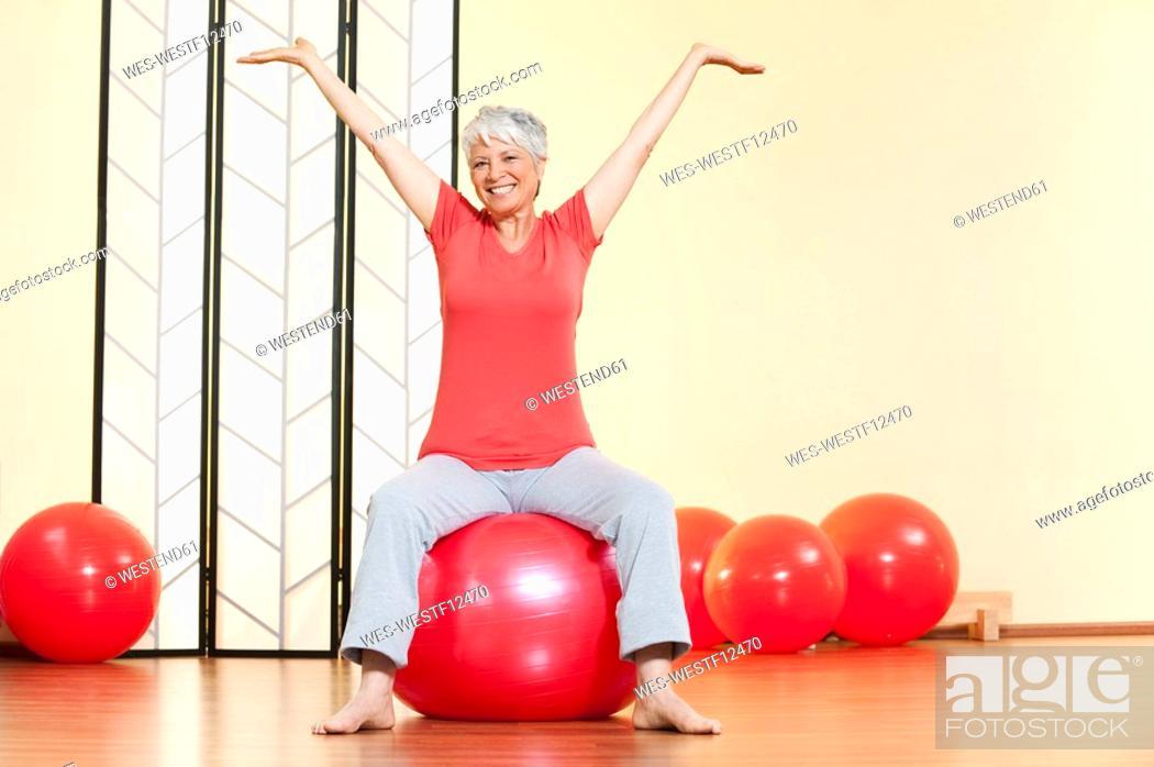 Stock Photo: Senior woman sitting on gymnastic ball, smiling, portrait.