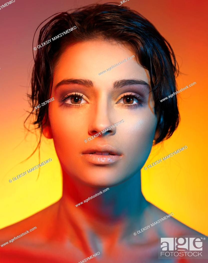 Stock Photo: Artistic beauty portrait of a young woman beautiful face with short dark hair lit with colorful, red and yellow lights.