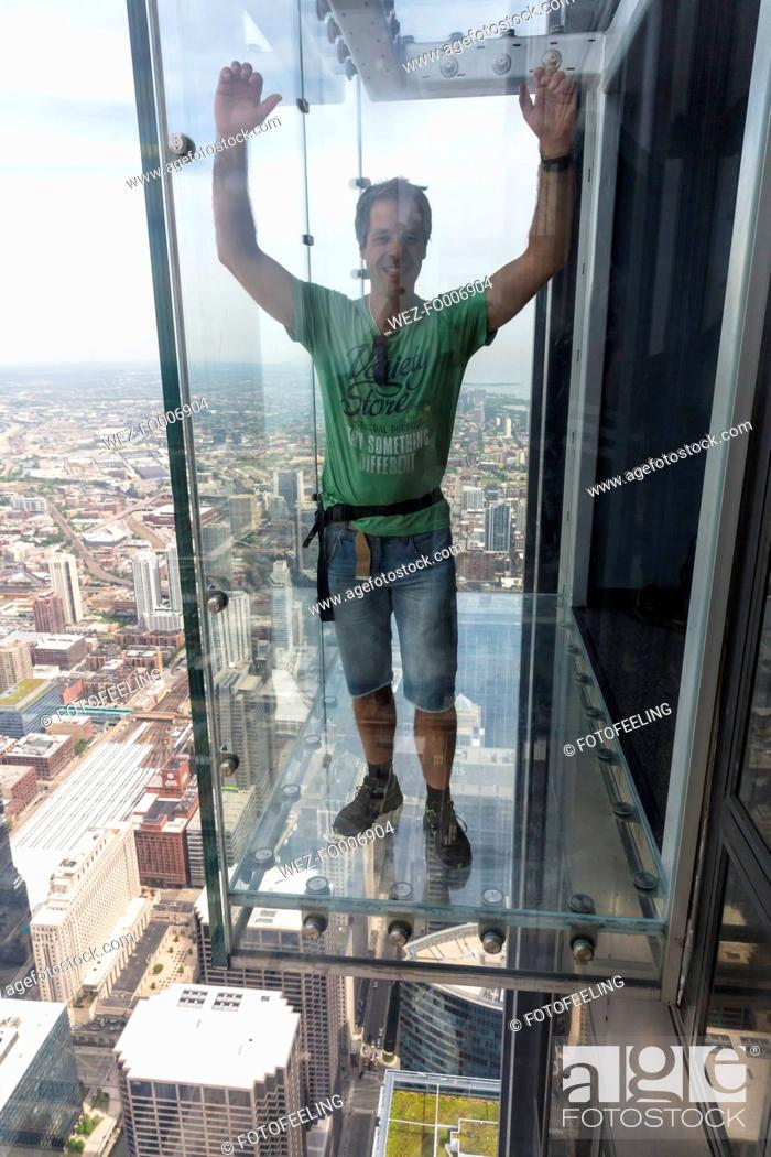 Imagen: Chicago, Illinois, Chicago, Tourist on glass balcony of Willis Tower.