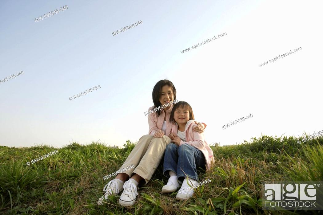 Stock Photo: Portrait of a mother sitting with daughter on grass.