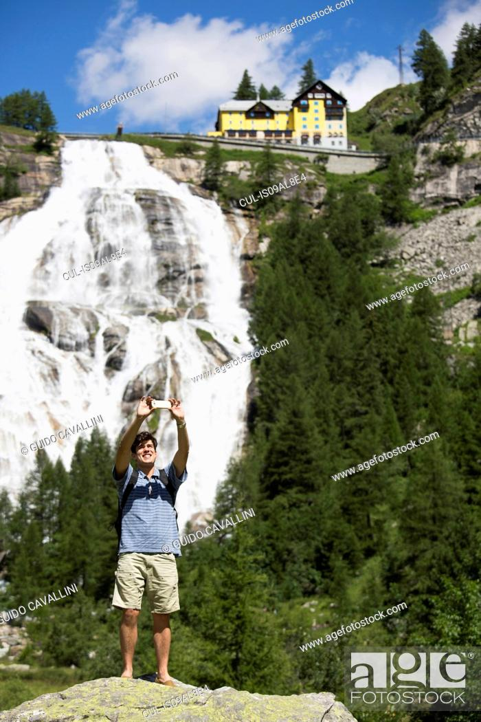 Stock Photo: Young man taking smartphone selfie in front of Toce waterfall, Formazza, Verbania, Piemonte, Italy.