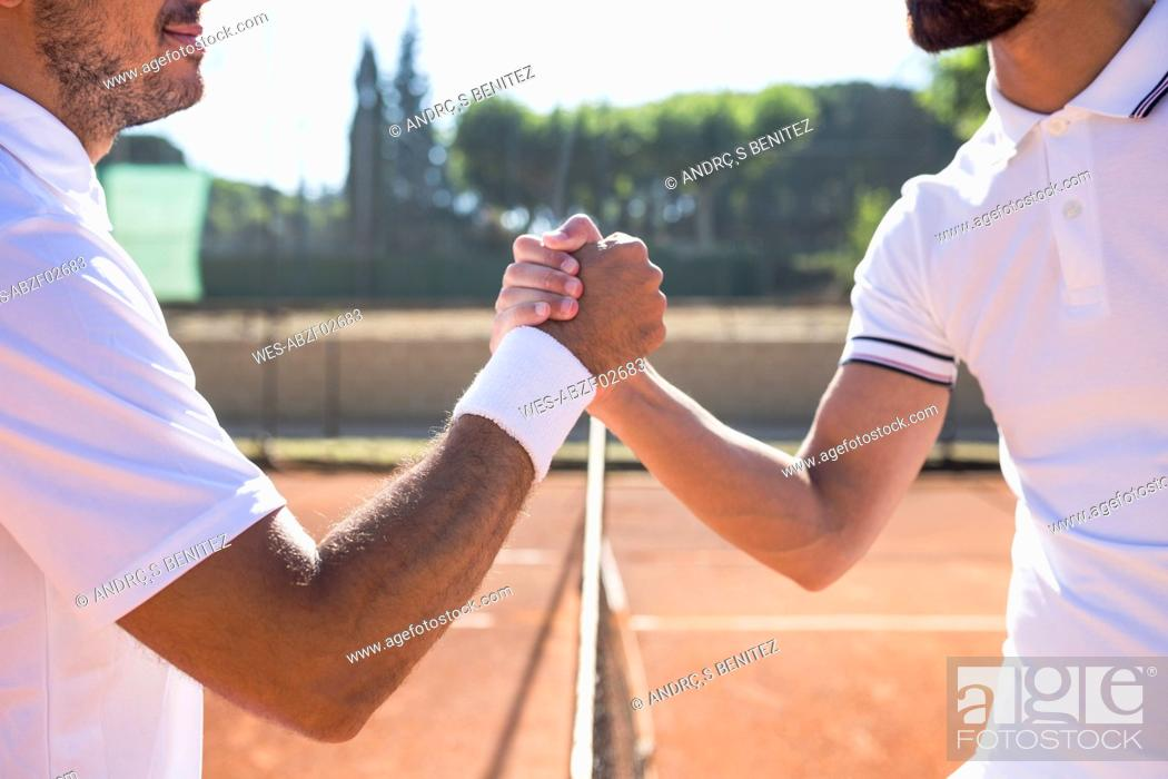 Photo de stock: Side view of two tennis players with rackets shaking hands and smiling before tennis match.