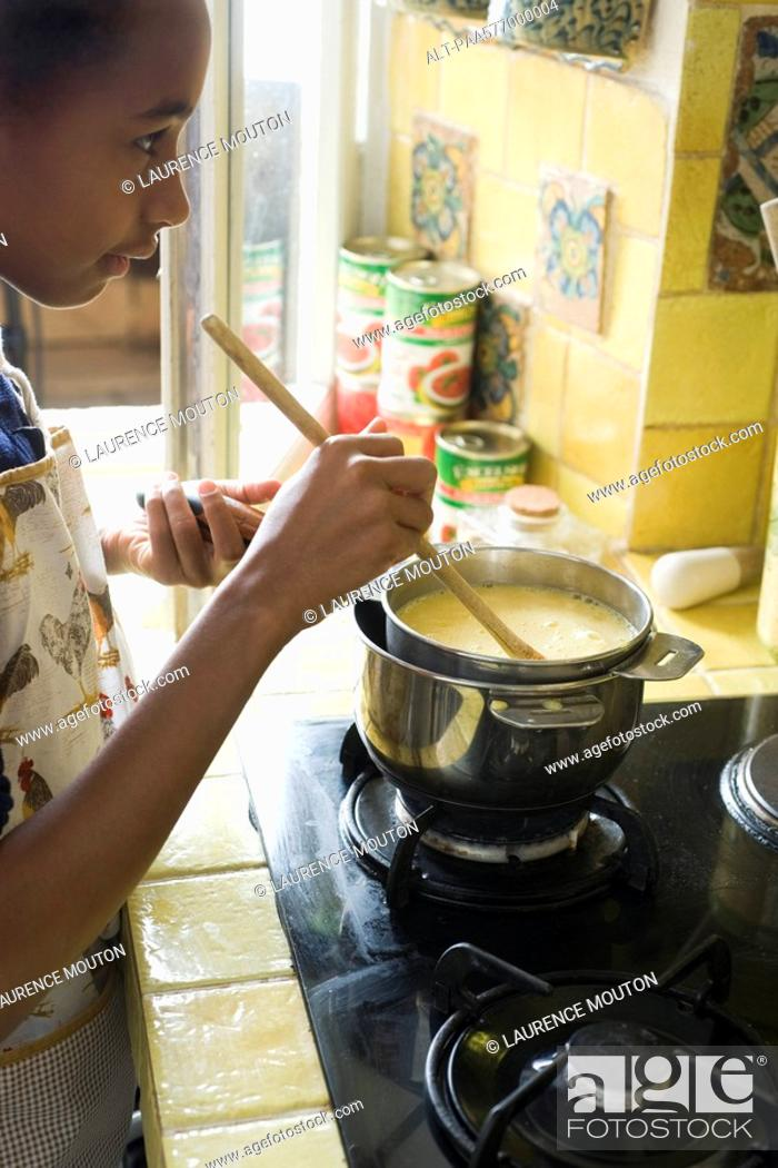 Stock Photo: Girl stirring pot on stove.