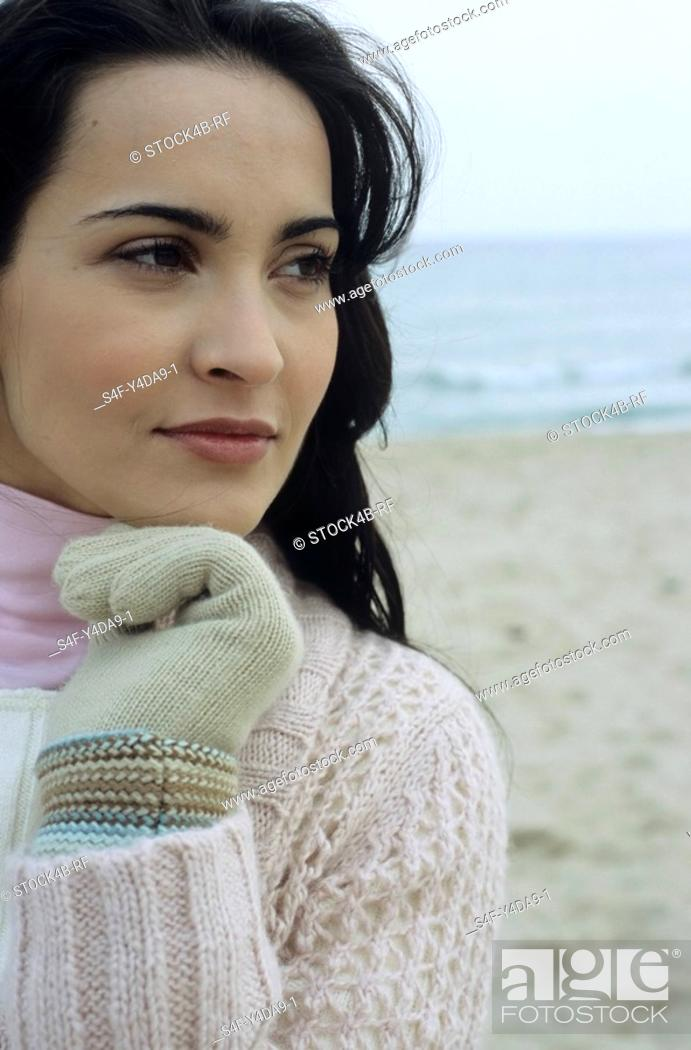 Stock Photo: Young brownhaired Woman with Gloves and Cardigan at the Beach - Holiday - Temperature.