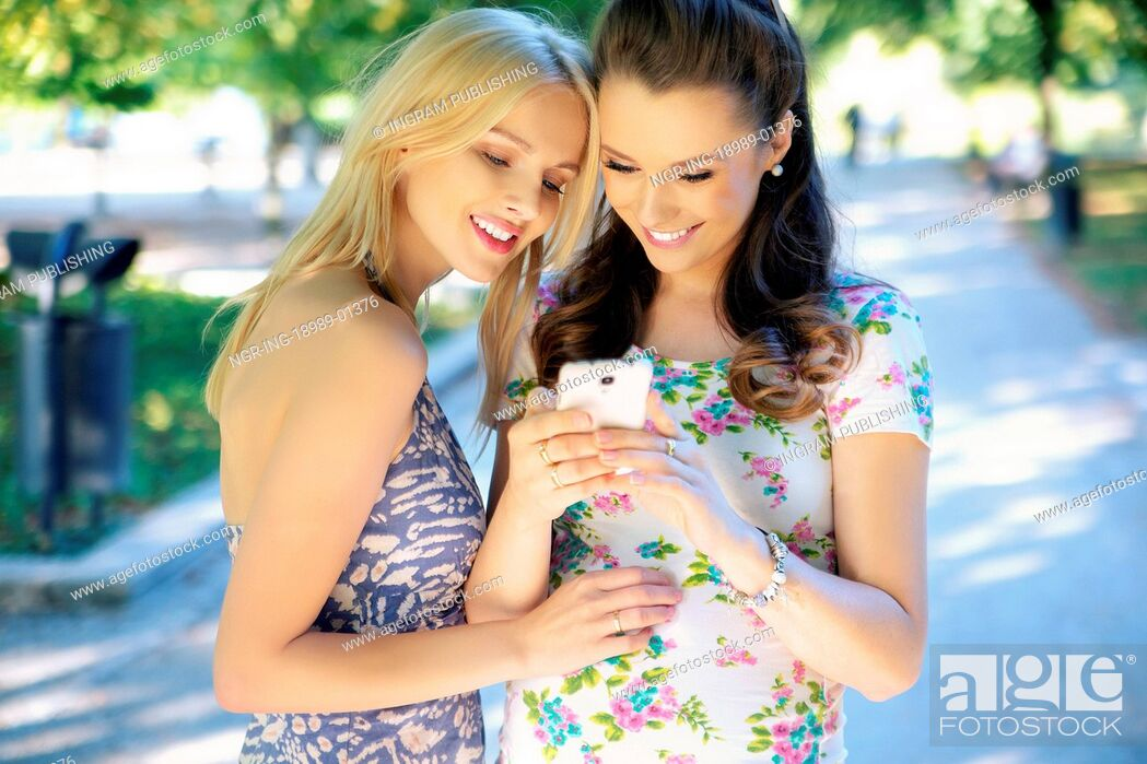 Stock Photo: Two young women texting their girlfriend.