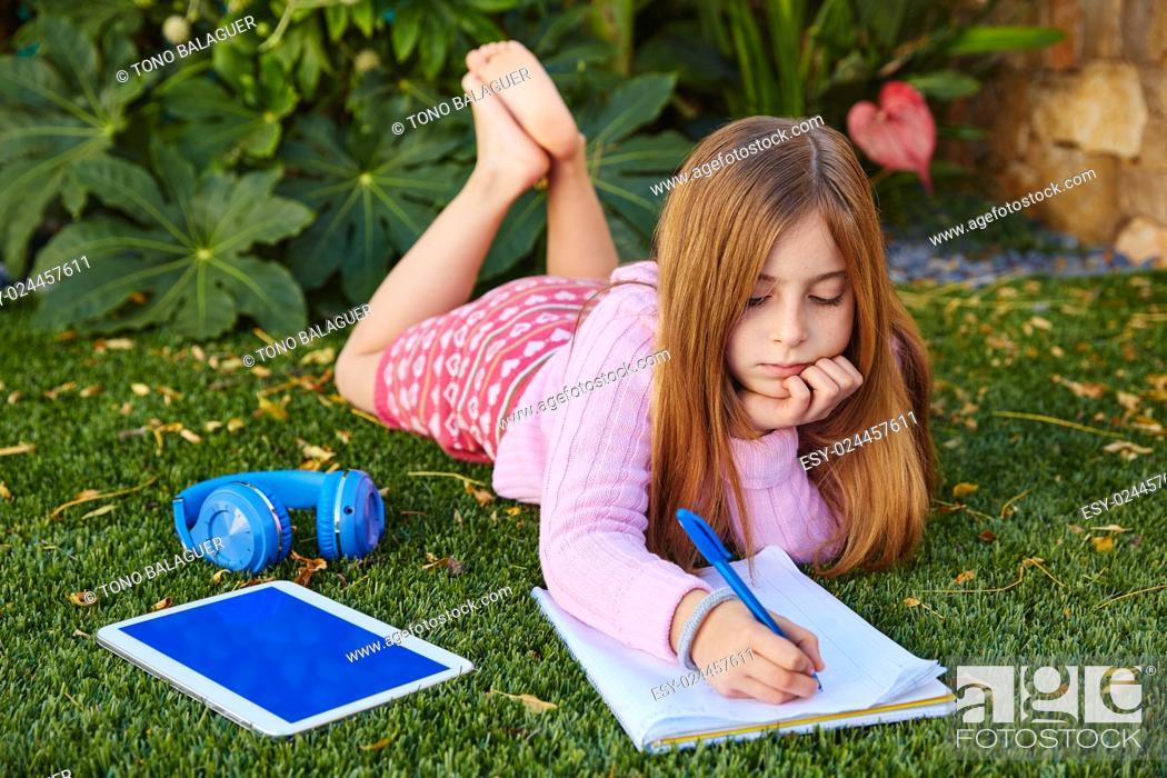 Imagen: Blond kid girl homework lying on grass turf writting notebook.