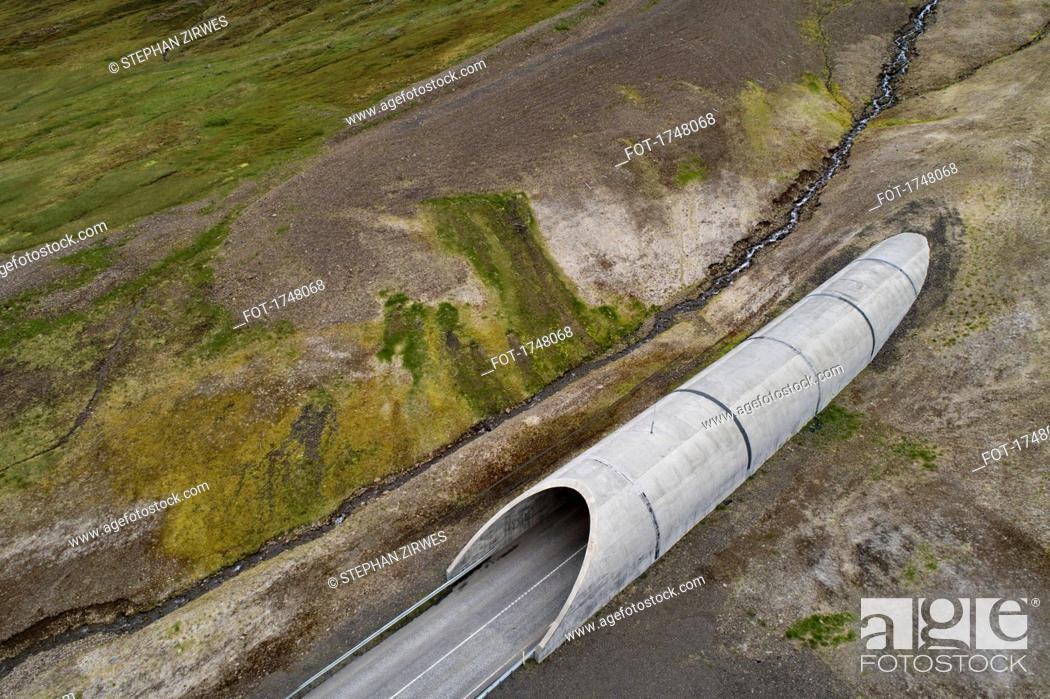 Stock Photo: Drone view of tunnel through landscape, Iceland.