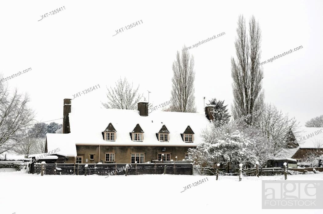 Stock Photo: A row of tied cottages in the snow  Tackley in the Cotswolds.