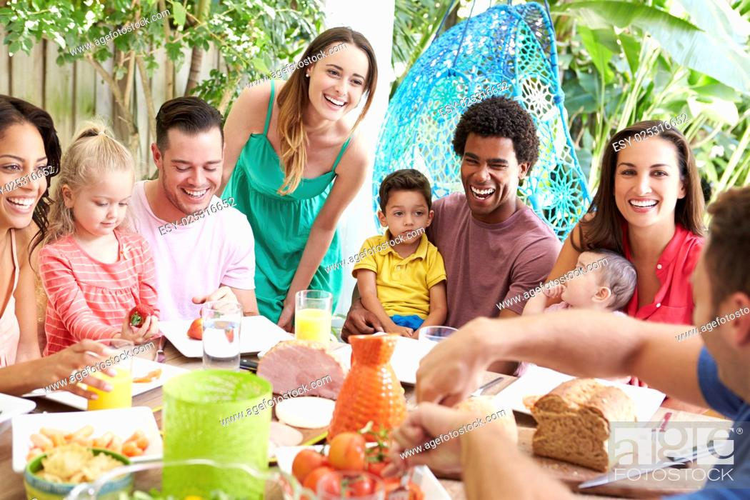 Imagen: Group Of Families Enjoying Outdoor Meal At Home.