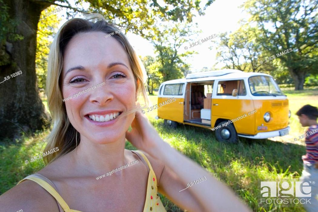 Stock Photo: Young woman in field by camper van, smiling, portrait, close-up.