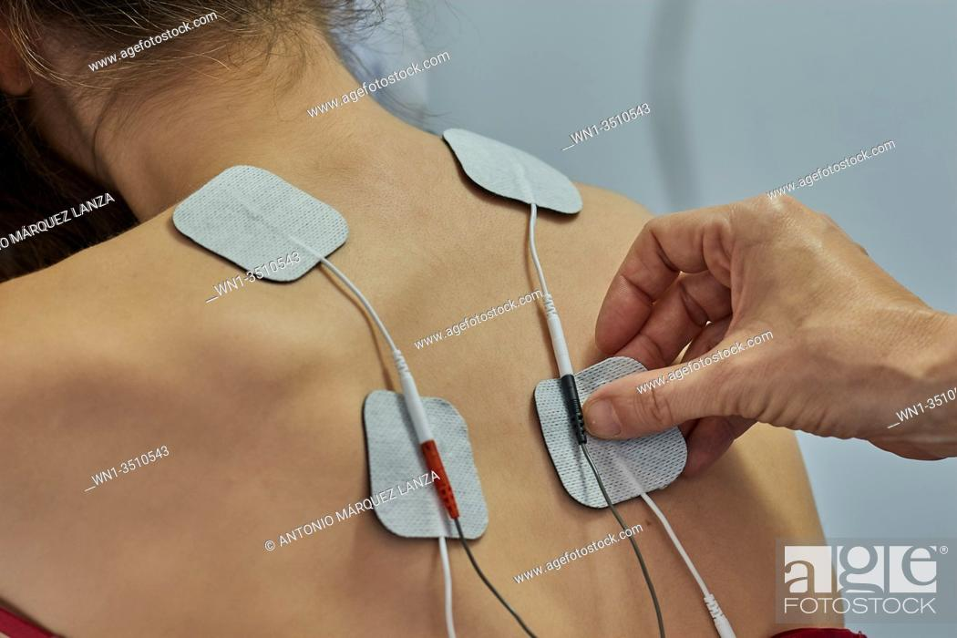 Stock Photo: Electro stimulation in physical therapy to a young woman. Medical check at the shoulder in a physiotherapy center. Tens therapy.