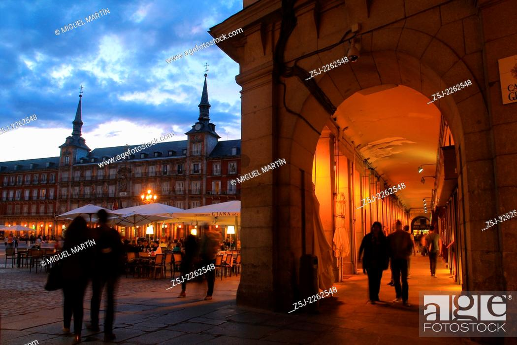 Stock Photo: Cloudy twilight on the Plaza Mayor of Madrid seen from Gerona street next to some of many restaurants placed under the porticoes facing the square.