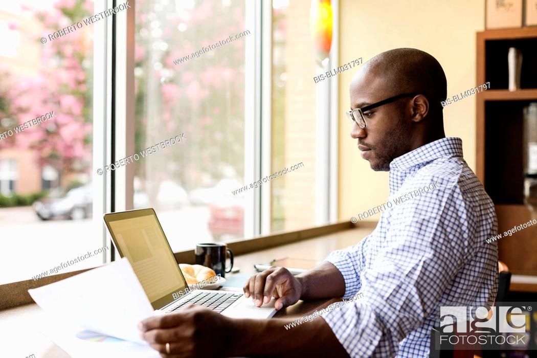 Imagen: Black man using laptop in coffee shop.