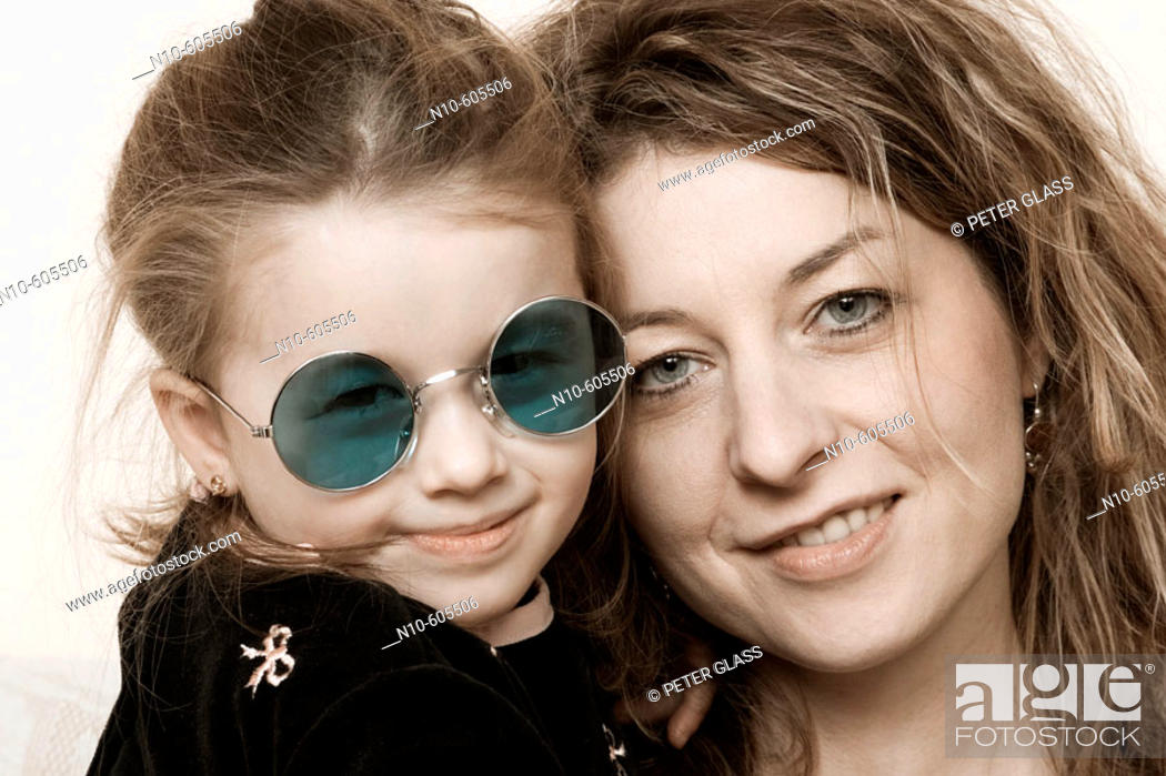 Stock Photo: Young girl, wearing sunglasses, sitting with her mother.