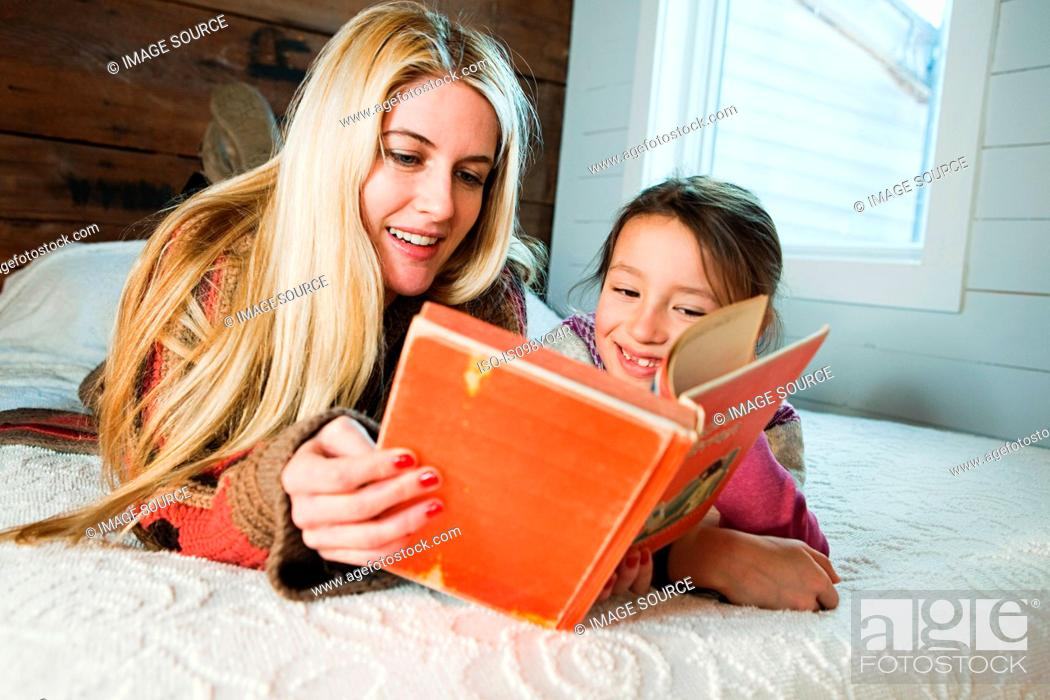 Stock Photo: Mother and daughter lying on bed reading book.