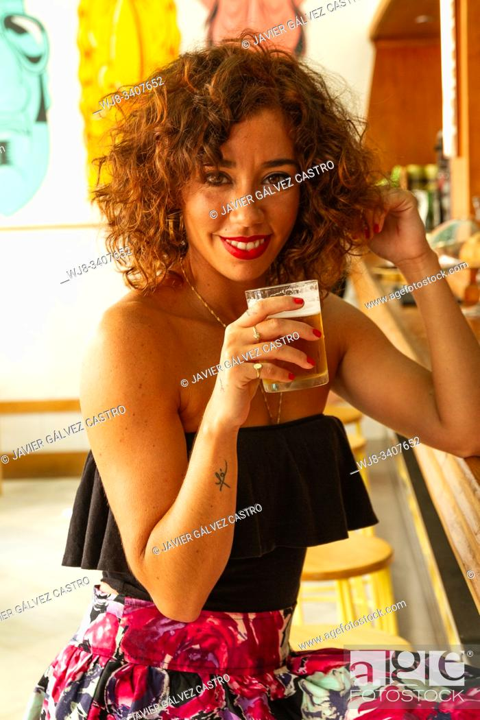 Stock Photo: Young woman looking at camera while holding a beer, smiling, wearing a black top.